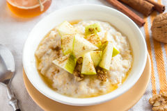 Oatmeal porridge with apples, honey, nuts and cinnamon Stock Photo