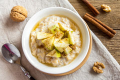 Oatmeal porridge with apples, honey, nuts and cinnamon Stock Photos