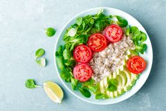 Oatmeal porridge with avocado and vegetable salad of fresh tomatoes and lettuce. Healthy dietary breakfast. Top view stock photos