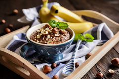 Oatmeal porridge with banana, hazelnut, chocolate and honey stock photos