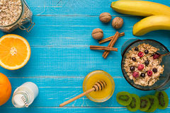 Oatmeal porridge with banana, kiwi fruit, nuts and honey in a bowl with egg for healthy breakfast on rustic wooden Stock Photography