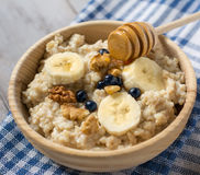 Oatmeal porridge with bananas, blueberries and honey stock images
