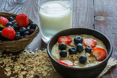 Oatmeal porridge with berries and glass of milk on wooden table Stock Photos