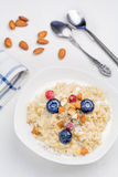 Oatmeal porridge with berries and nuts in bowl, top view Stock Photos