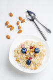 Oatmeal porridge with berries and nuts in bowl, top view Royalty Free Stock Photography