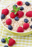 Oatmeal porridge  with berries. Raspberries and blueberries. Stock Photo