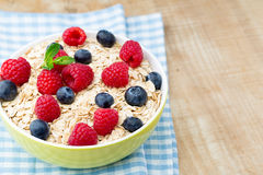 Oatmeal porridge with berries. Raspberries and blueberries. Royalty Free Stock Photos