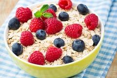 Oatmeal porridge with berries. Raspberries and blueberries. Stock Photography
