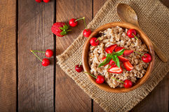 Oatmeal porridge with berries. In a wooden bowl Stock Images