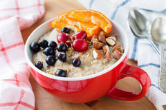 Oatmeal porridge with black currants, cranberries, nuts and orange Stock Images
