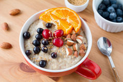Oatmeal porridge with black currants, cranberries, nuts and orange Stock Photos