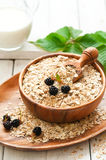 Oatmeal porridge. Oatmeal with blackberry and milk for breakfast on white background, selective focus stock photo
