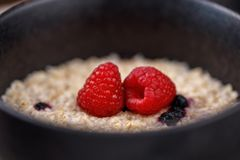 Oatmeal porridge with blueberries and fresh raspberries in a delicious bowl. Close-up Stock Photography