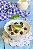 Oatmeal porridge with blueberry in a white bowl. Stock Photos