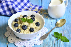 Oatmeal porridge with blueberry in a white bowl. Stock Photography