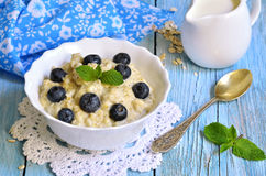 Oatmeal porridge with blueberry in a white bowl. Stock Photos