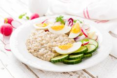 Oatmeal porridge with boiled egg and vegetable salad with fresh radish, cucumber and lettuce. Healthy dietary breakfast. Closeup royalty free stock photos