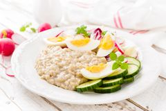 Oatmeal porridge with boiled egg and vegetable salad with fresh radish, cucumber and lettuce. Healthy dietary breakfast. Closeup stock images