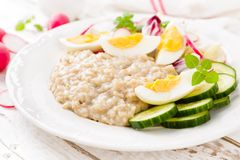 Oatmeal porridge with boiled egg and vegetable salad with fresh radish, cucumber and lettuce. Healthy dietary breakfast. Closeup stock photography