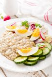 Oatmeal porridge with boiled egg and vegetable salad with fresh radish, cucumber and lettuce. Healthy dietary breakfast. Closeup royalty free stock image