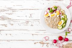 Oatmeal porridge with boiled egg and vegetable salad with fresh radish, cucumber and lettuce. Healthy dietary breakfast. Top view stock photos