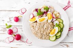 Oatmeal porridge with boiled egg and vegetable salad with fresh radish, cucumber and lettuce. Healthy dietary breakfast. Top view stock images