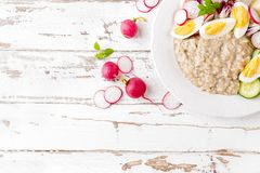 Oatmeal porridge with boiled egg and vegetable salad with fresh radish, cucumber and lettuce. Healthy dietary breakfast. Top view stock photography