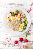 Oatmeal porridge with boiled egg and vegetable salad with fresh radish, cucumber and lettuce. Healthy dietary breakfast. Top view stock photo