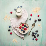 Oatmeal porridge, bottle of milk and berries on blue wooden background with kitchen towel Stock Photos