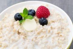 Oatmeal porridge in bowl with berries raspberries and blackberri Stock Photography