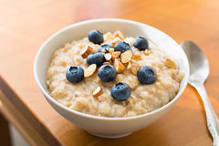 Oatmeal porridge in bowl with blueberries and nuts Royalty Free Stock Photo