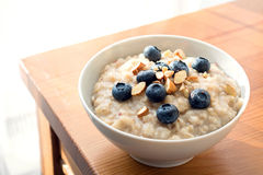 Oatmeal porridge in bowl with blueberries and nuts Royalty Free Stock Images