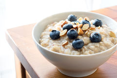 Oatmeal porridge in bowl with blueberries and nuts Stock Photography