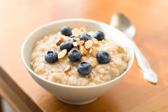 Oatmeal porridge in bowl with blueberries and nuts Stock Photos