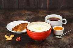 Oatmeal porridge in bowl, stuffed crepe and tea. Tasty breakfast Royalty Free Stock Images