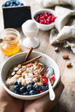 Oatmeal porridge bowl with superfoods in hands. Hands holding bowl of oat porridge with blueberries, almonds, linseed, cinnamon and currants. Selective focus Stock Photos