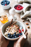 Oatmeal porridge bowl with superfoods in hands. Hands holding bowl of oat porridge with blueberries, almonds, linseed, cinnamon and currants. Selective focus Royalty Free Stock Images