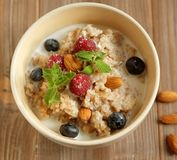 Oatmeal porridge in bowl topped with fresh blueberries and raspb. Erries on wooden table. Top view Stock Image