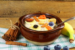 Oatmeal porridge in bowl topping with banana cinnamon blueberries dry fruits Stock Photos