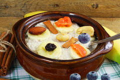 Oatmeal porridge in bowl topping with banana cinnamon blueberries dry fruits Stock Photo