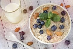 Oatmeal porridge.Breakfast cereals with blueberries and glass of royalty free stock photography
