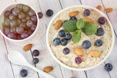 Oatmeal porridge.Breakfast cereals with blueberries and glass of stock image
