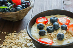 Oatmeal porridge in brown ceramic bowl with ripe berries. Raspberries and blueberries in wicker bowl Royalty Free Stock Photography