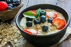 Oatmeal porridge in brown pottery bowl with ripe berries Stock Photography