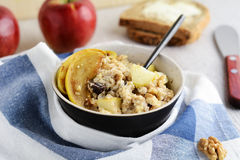Oatmeal porridge with caramelized apples, walnuts and raisins Stock Photography