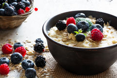 Oatmeal porridge in ceramic bowl with fresh ripe berries and mint Royalty Free Stock Images