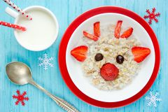 Oatmeal porridge for Christmas breakfast. Oatmeal porridge deer with strawberry and chocolate, fun food art idea for kids Royalty Free Stock Images
