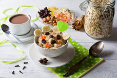 Oatmeal porridge with dried fruits, cranberries, bananas and spices. Cup of cacao and jar of oatmeal on background. Stock Photo
