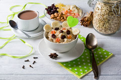 Oatmeal porridge with dried fruits, cranberries, bananas and spices. Cup of cacao and jar of oatmeal on background. Stock Photography