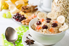 Oatmeal porridge with dried fruits, cranberries, bananas and spices. Jar of oatmeal on background. Arranged on white background Royalty Free Stock Image